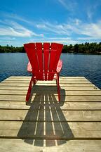 Red muskoka chair on dock