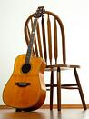 guitar resting against chair